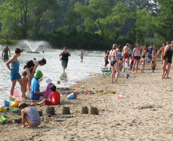 children and adults at the shore of the reservation swimming area